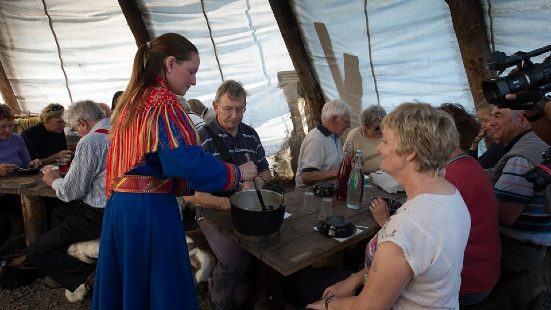 a sami girl giving food to guests