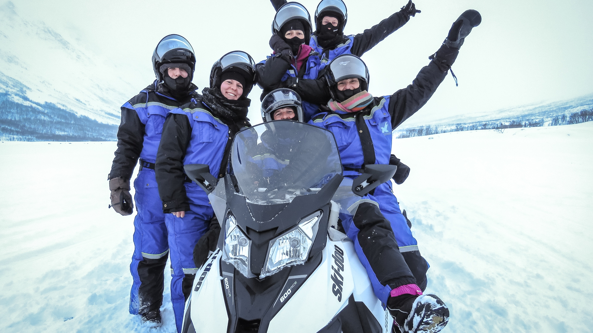 people sitting on a snowmobile