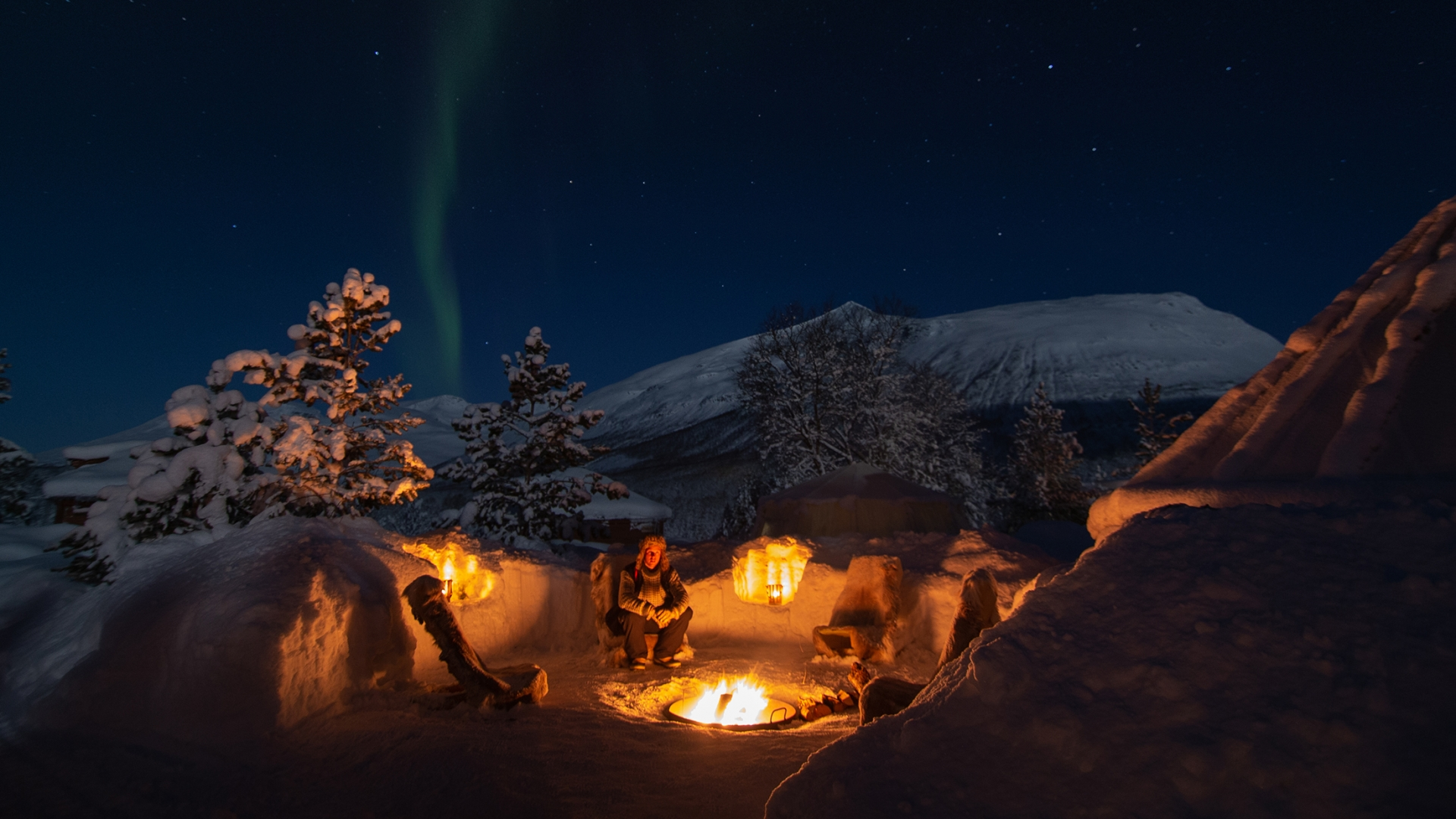 People around bonfire under the Northern Lights