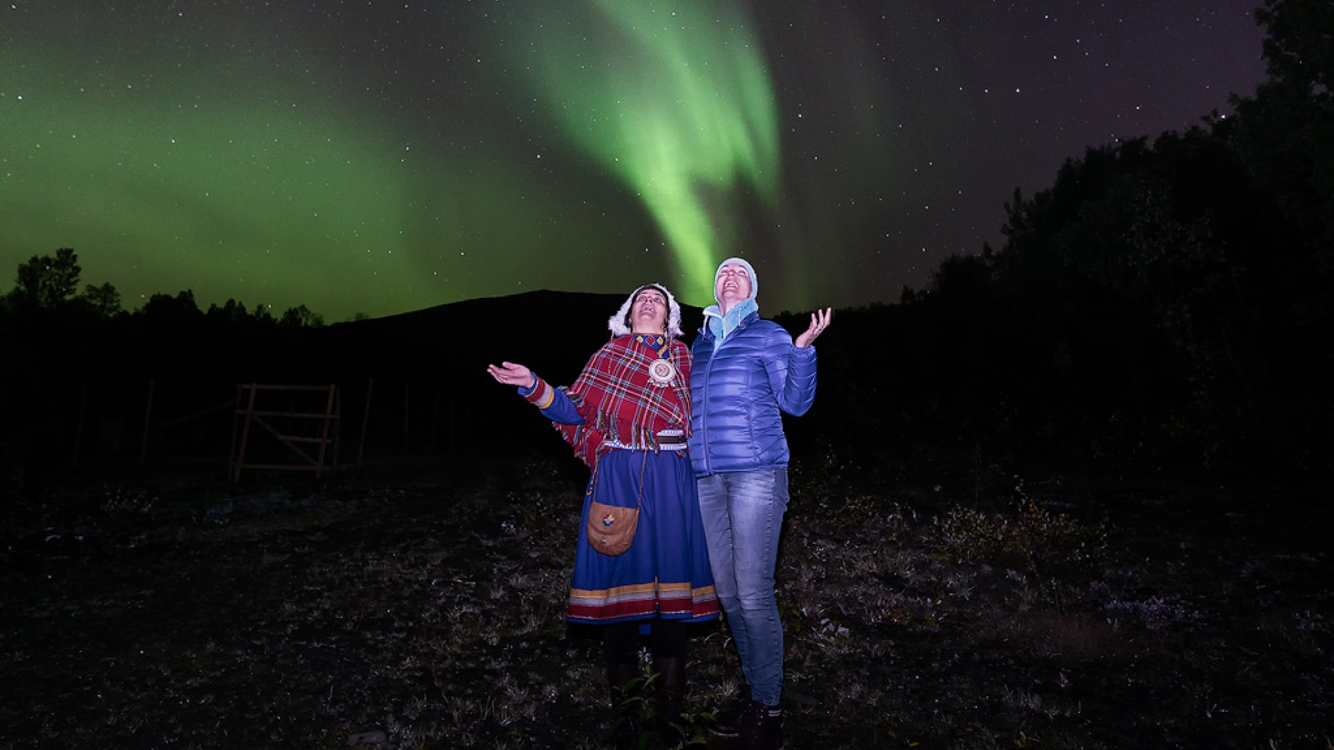 Man and woman in sami dress under the Northern Lights