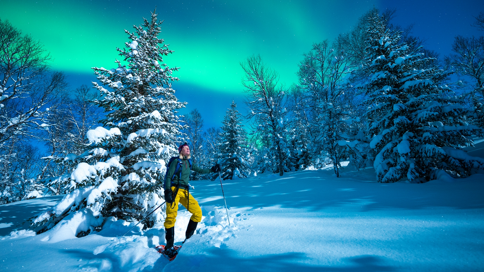 Woman out in the snow under the Northern Lights