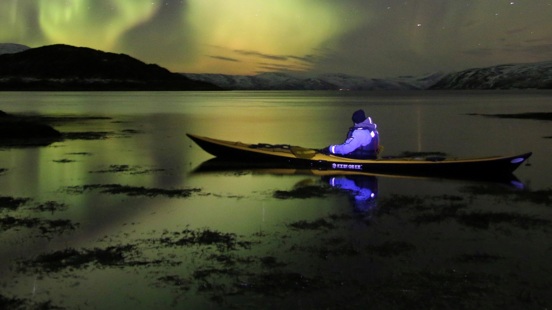 Man kayaking under the Northern Lights