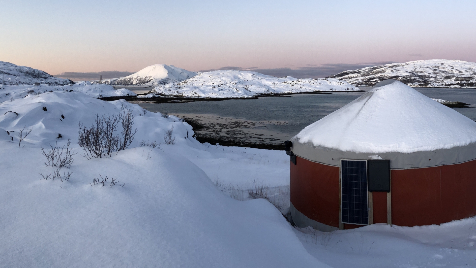 Yurts in snowy landscape by the ocean