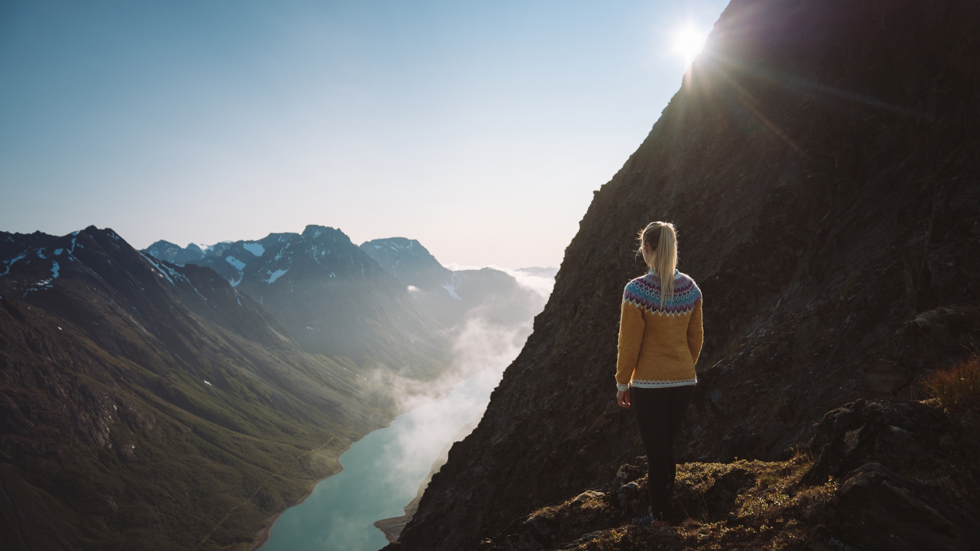 Woman standing at viewpoint on mountain in Lyngen