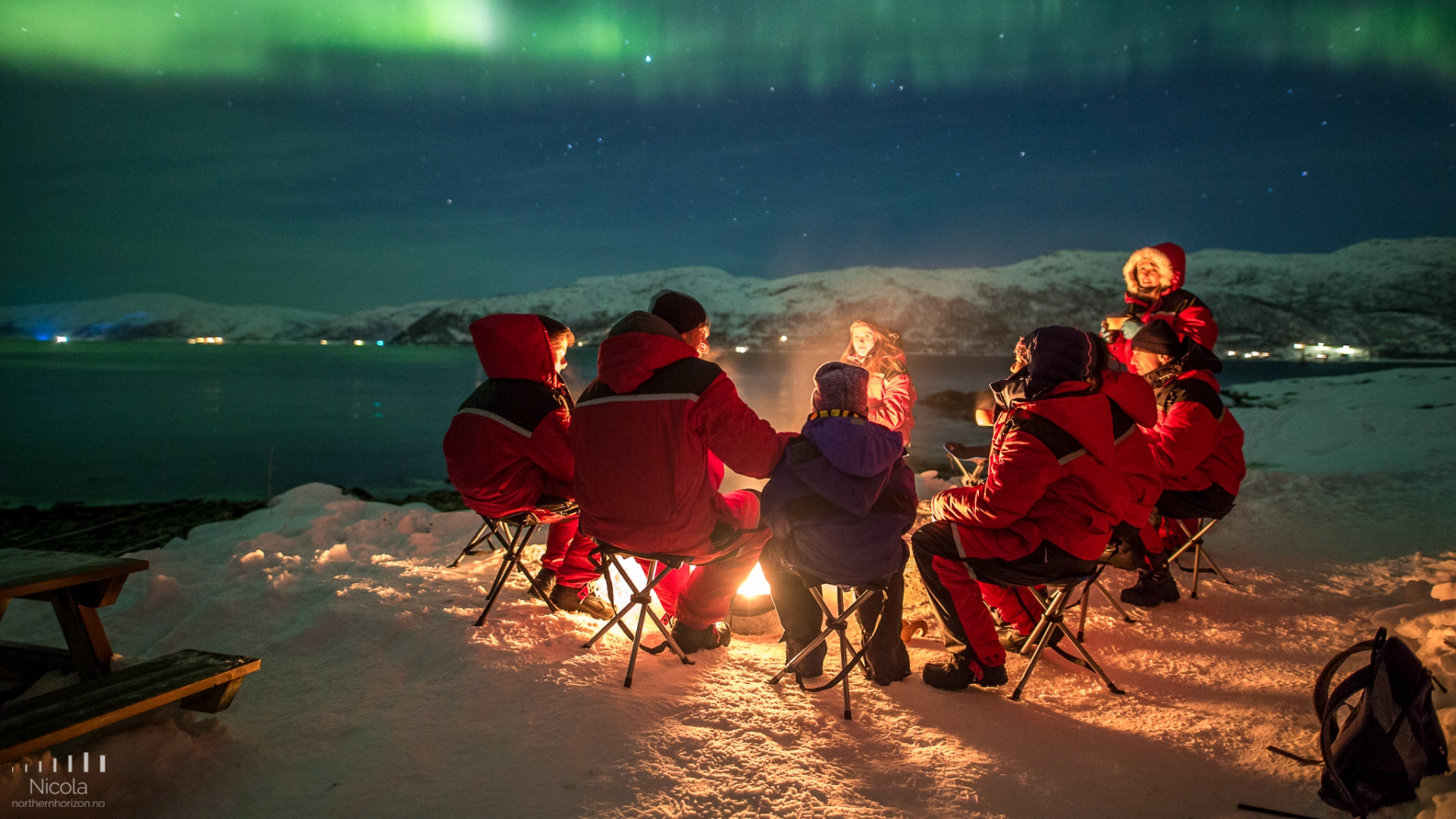 People around bonfire watching the Northern Lights