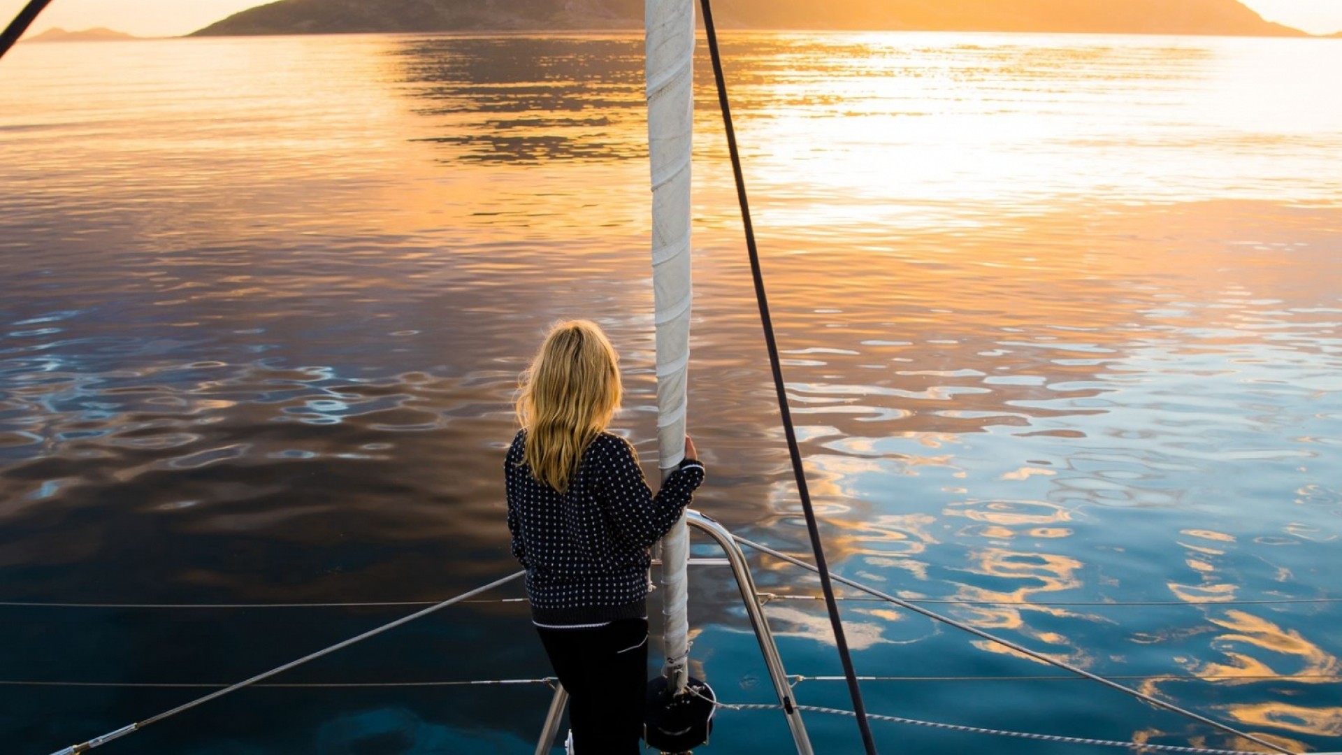 Woman standing on the edge of a boat in the Midnight Sun