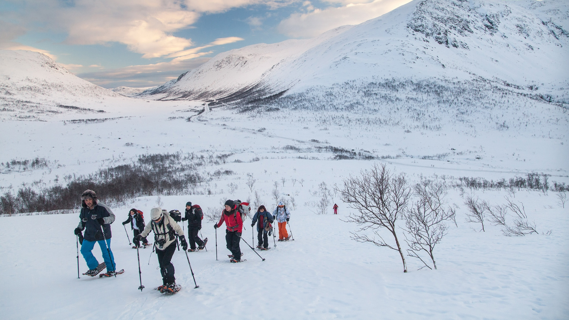 Group of people snowshoeing in winter landscape