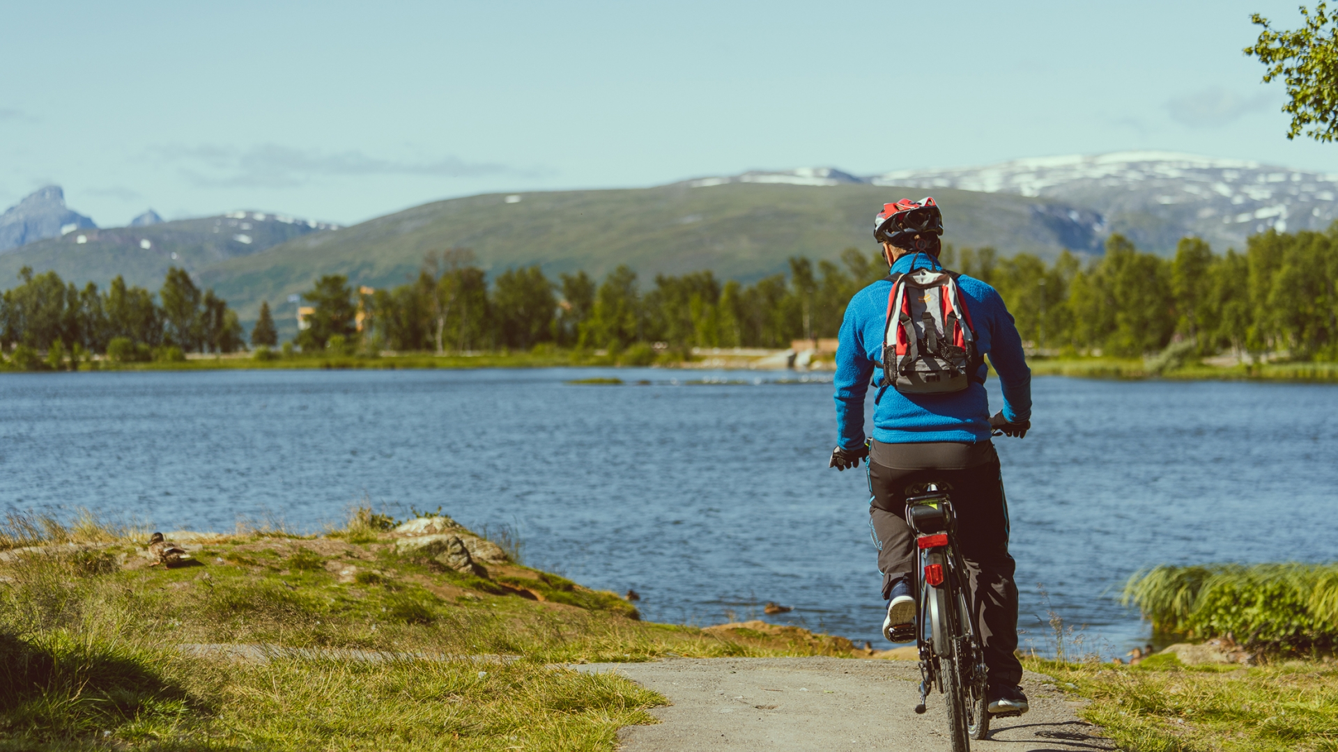 Man cycling around Prestvannet on Tromsø island