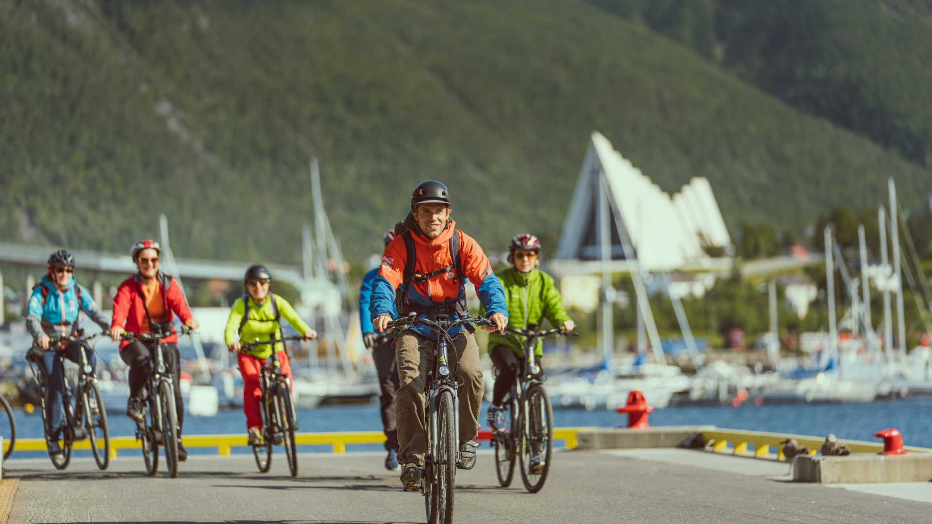Friends bicycling on the Tromsø Harbour with the Arctic Cathedral in the background