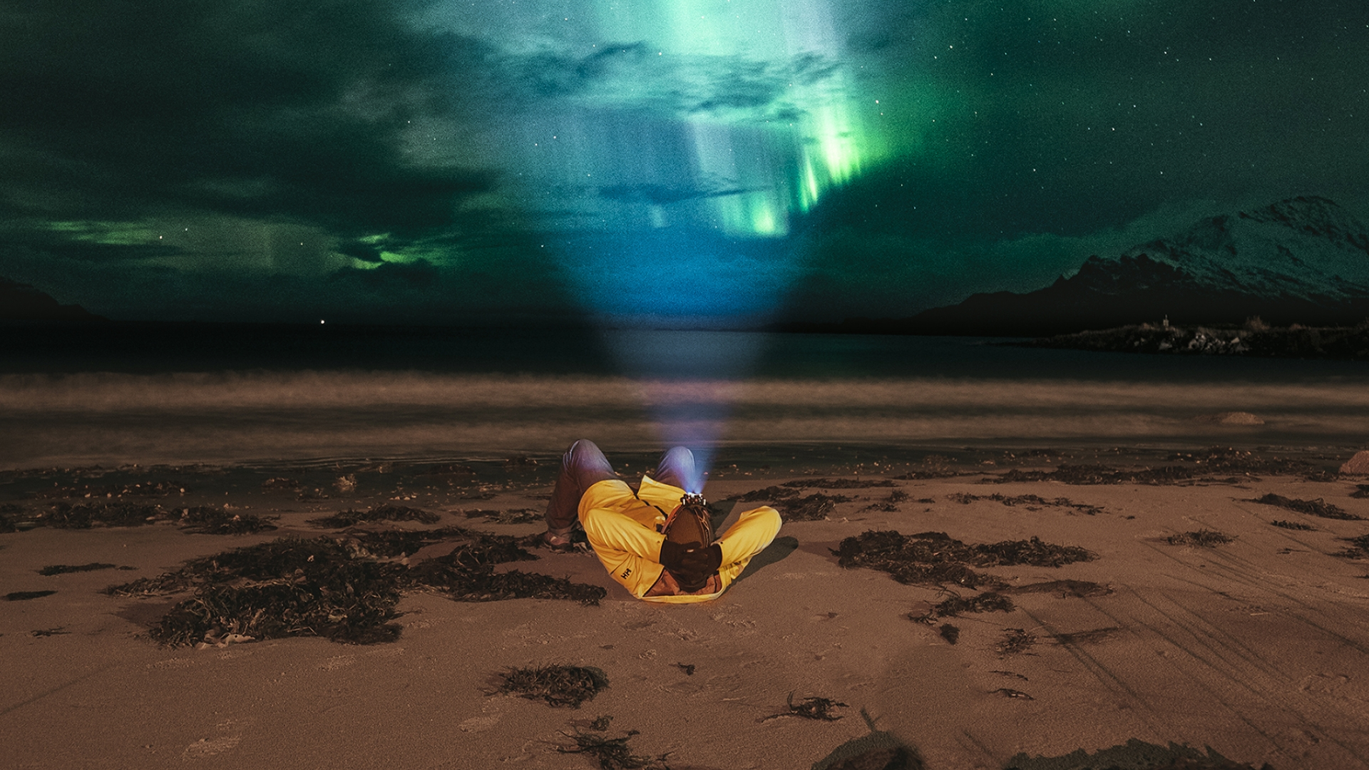 Man laying on the beach watching the Northern Lights