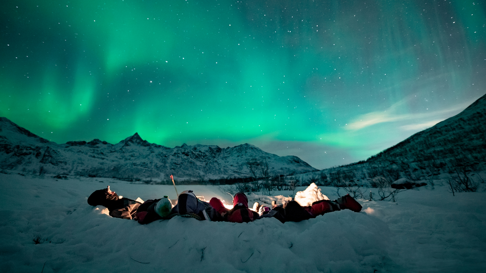 People watching the Northern Lights in the snow
