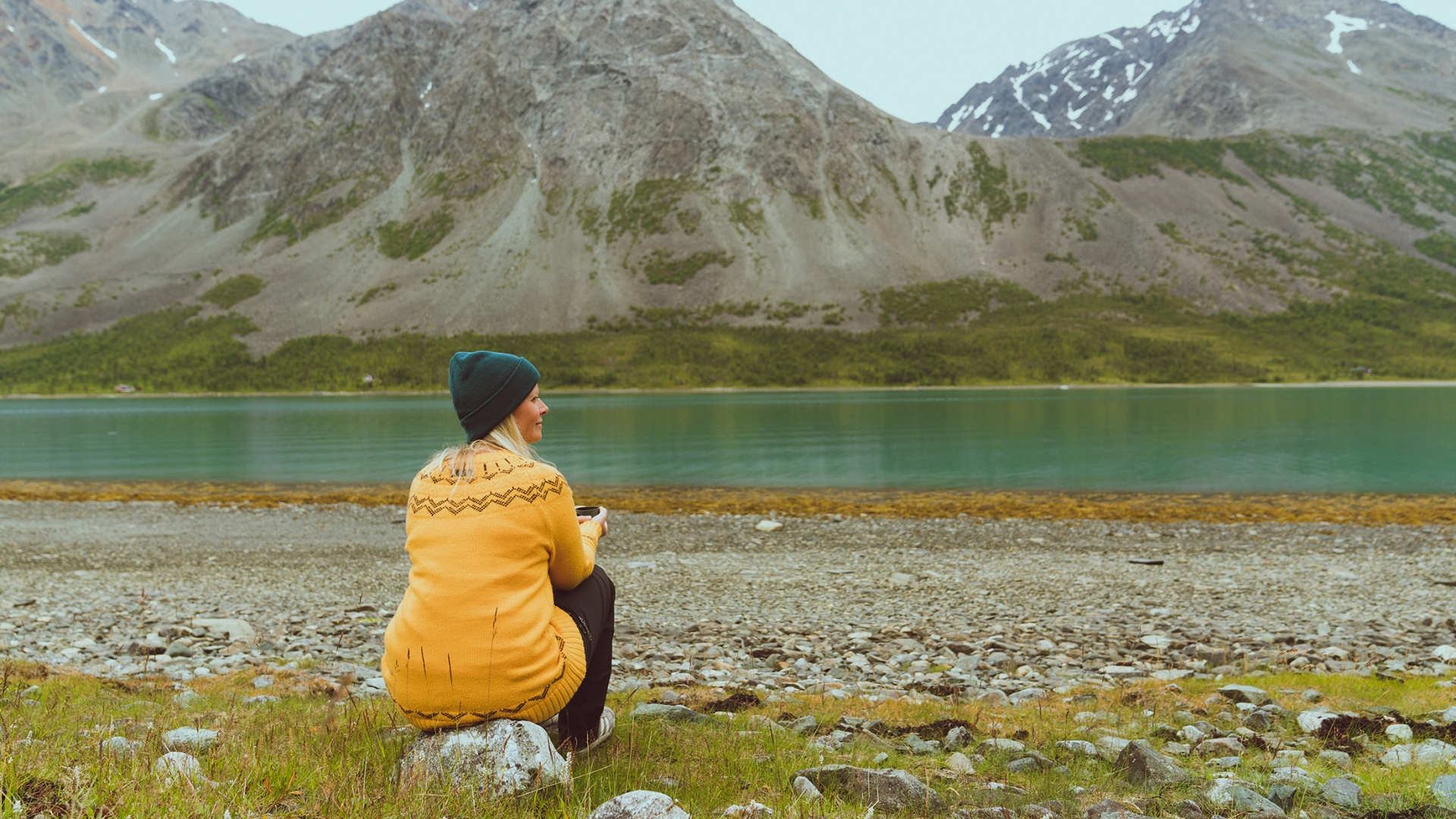 Woman enjoying peace and quiet next to lake in Lyngen