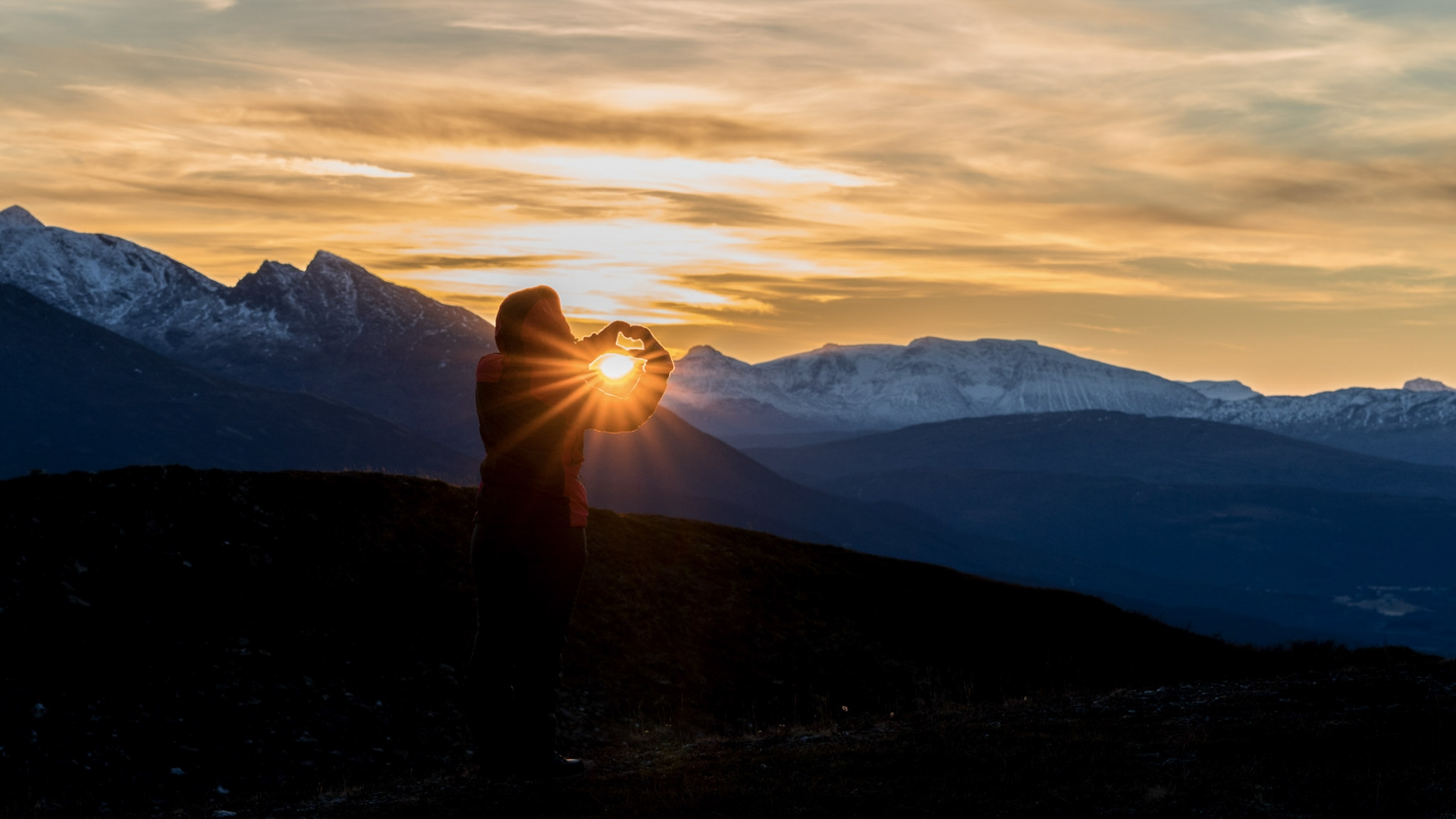Person on mountain with the Midnight Sun