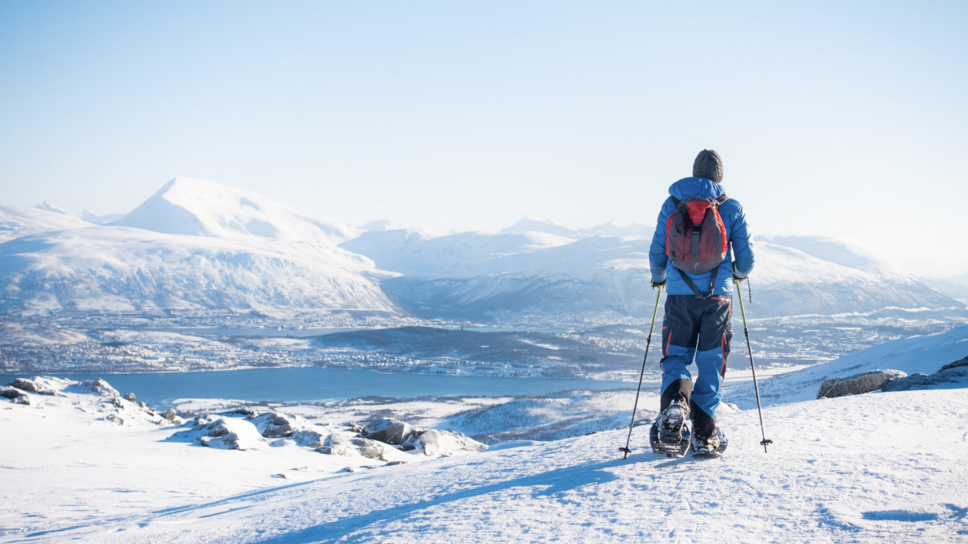 Man snowshoeing with views over mountains and fjords