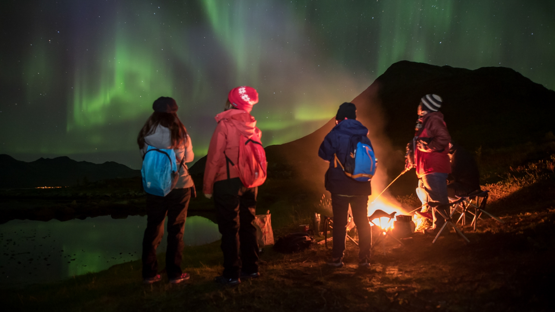 People standing by bonfire watching the Northern Lights
