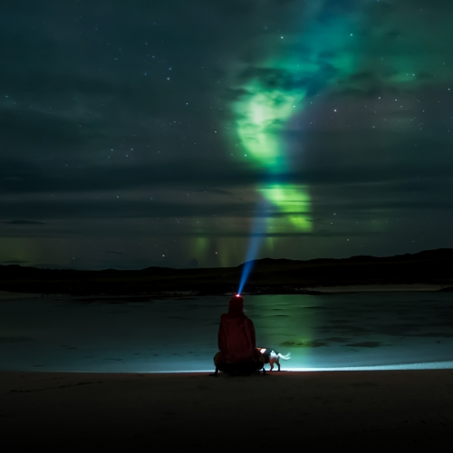 Man watching the Northern Lights from a beach
