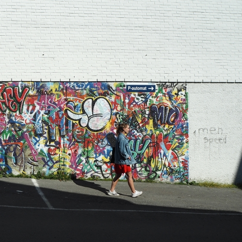 Woman walking in front of street art in Tromsø city centre