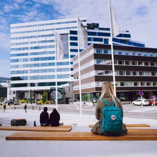 Woman sitting in front of The Edge hotel in Tromsø