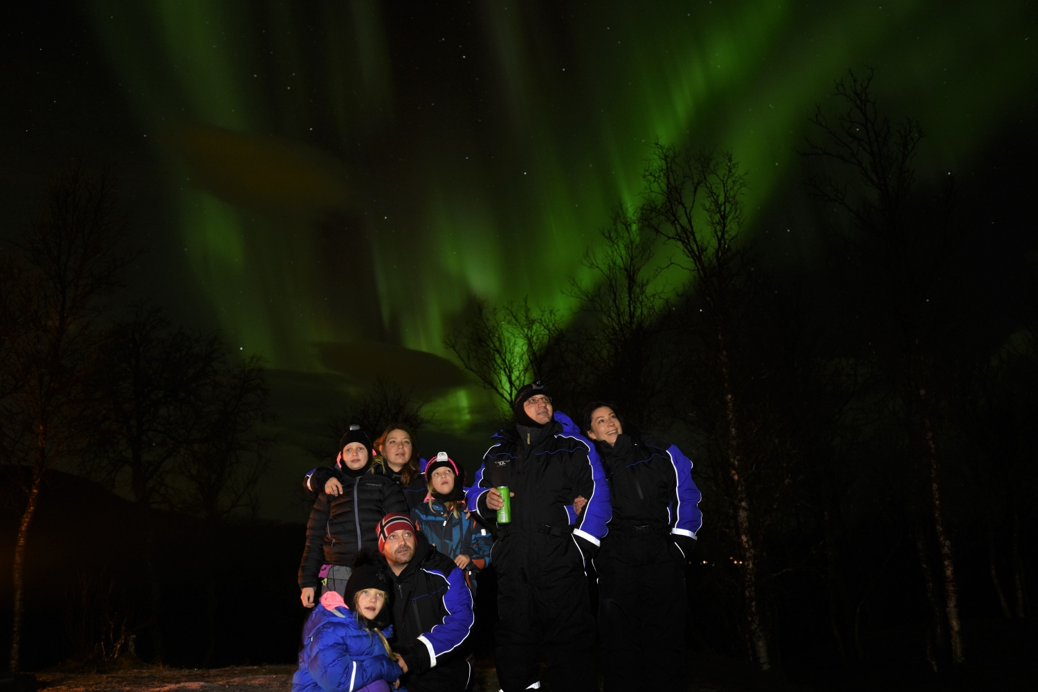 A group of people below the Northern Lights