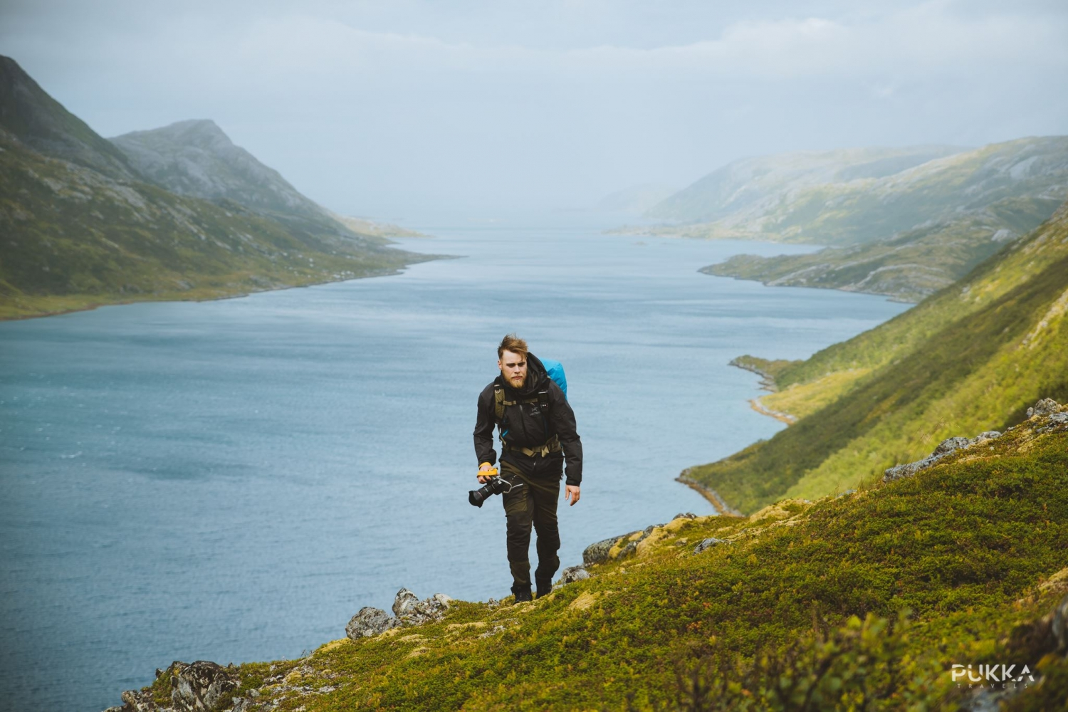 Man hiking on the mountain, fjord in the background