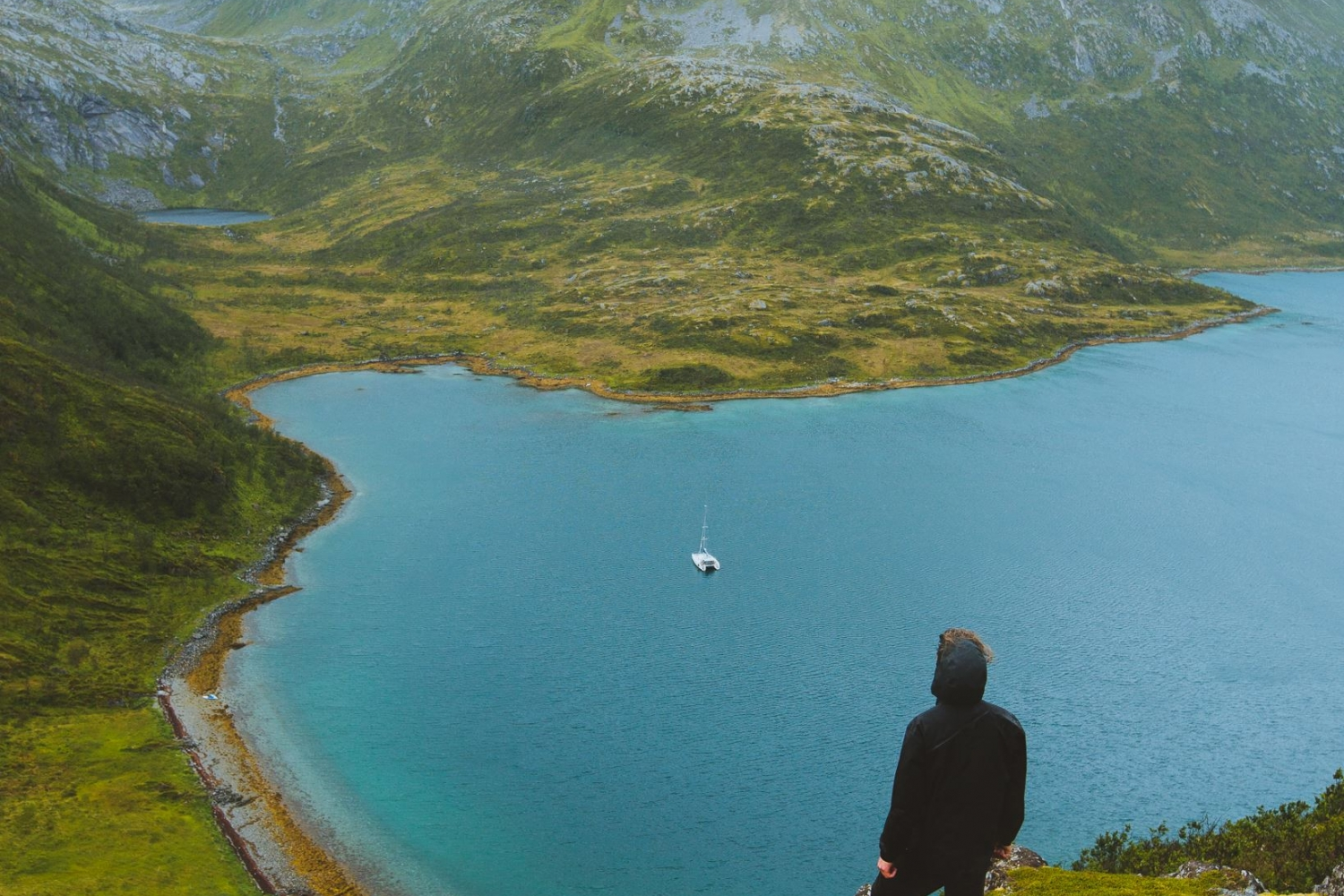 Man enjoying a great view over mountains, fjord and sea