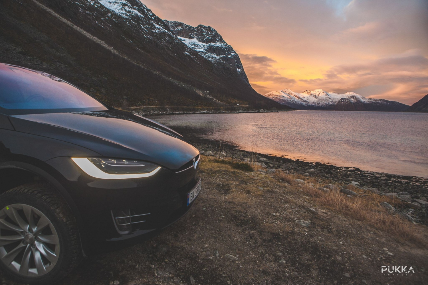 Tesla with colourful sky, sea and mountains in the background