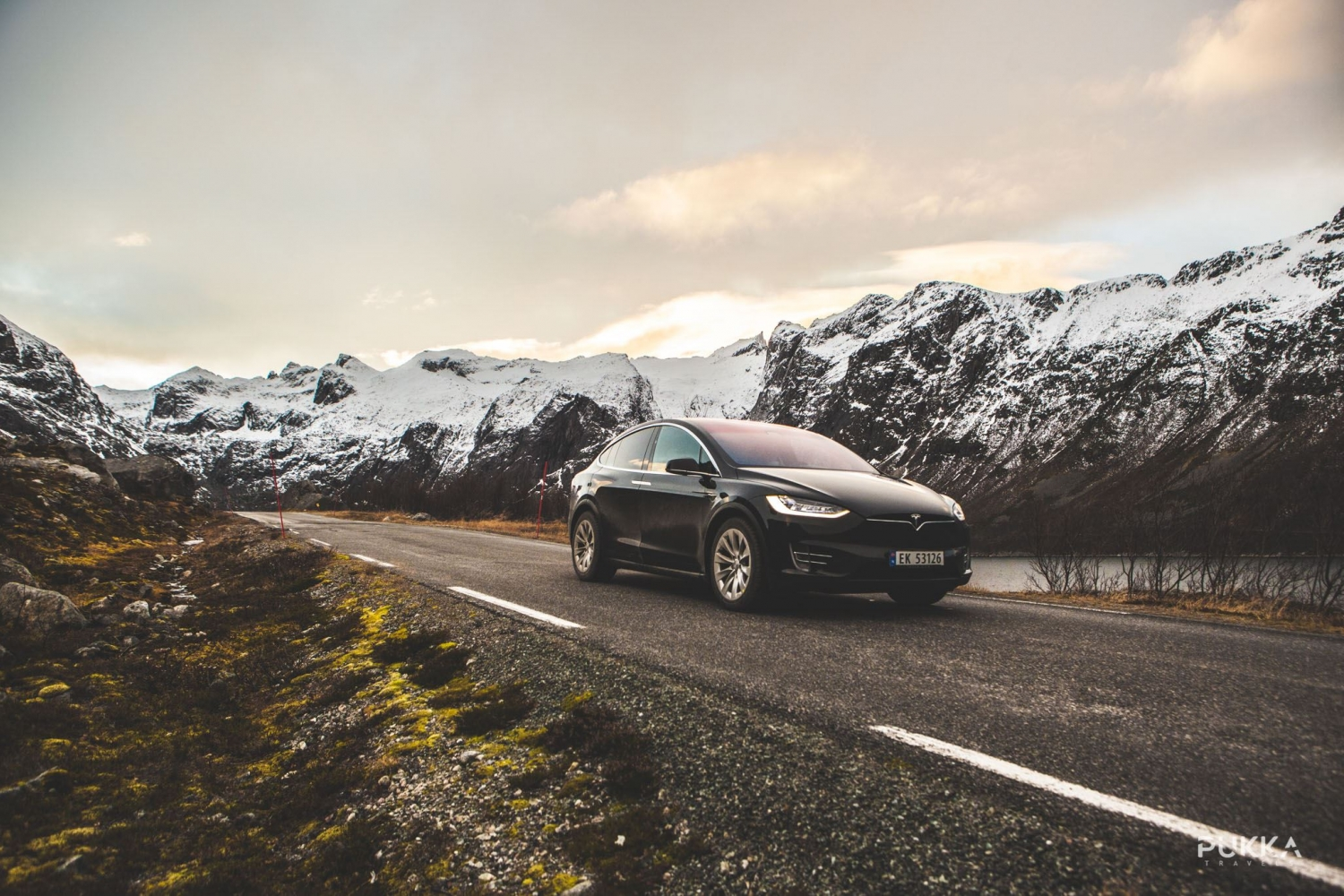 A black Tesla driving on a road with snowy hills in the background
