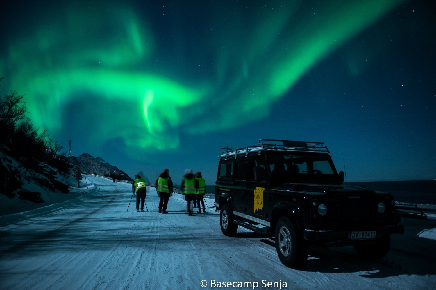 A truck parked on a snowy road with people and Northern Lights in the background