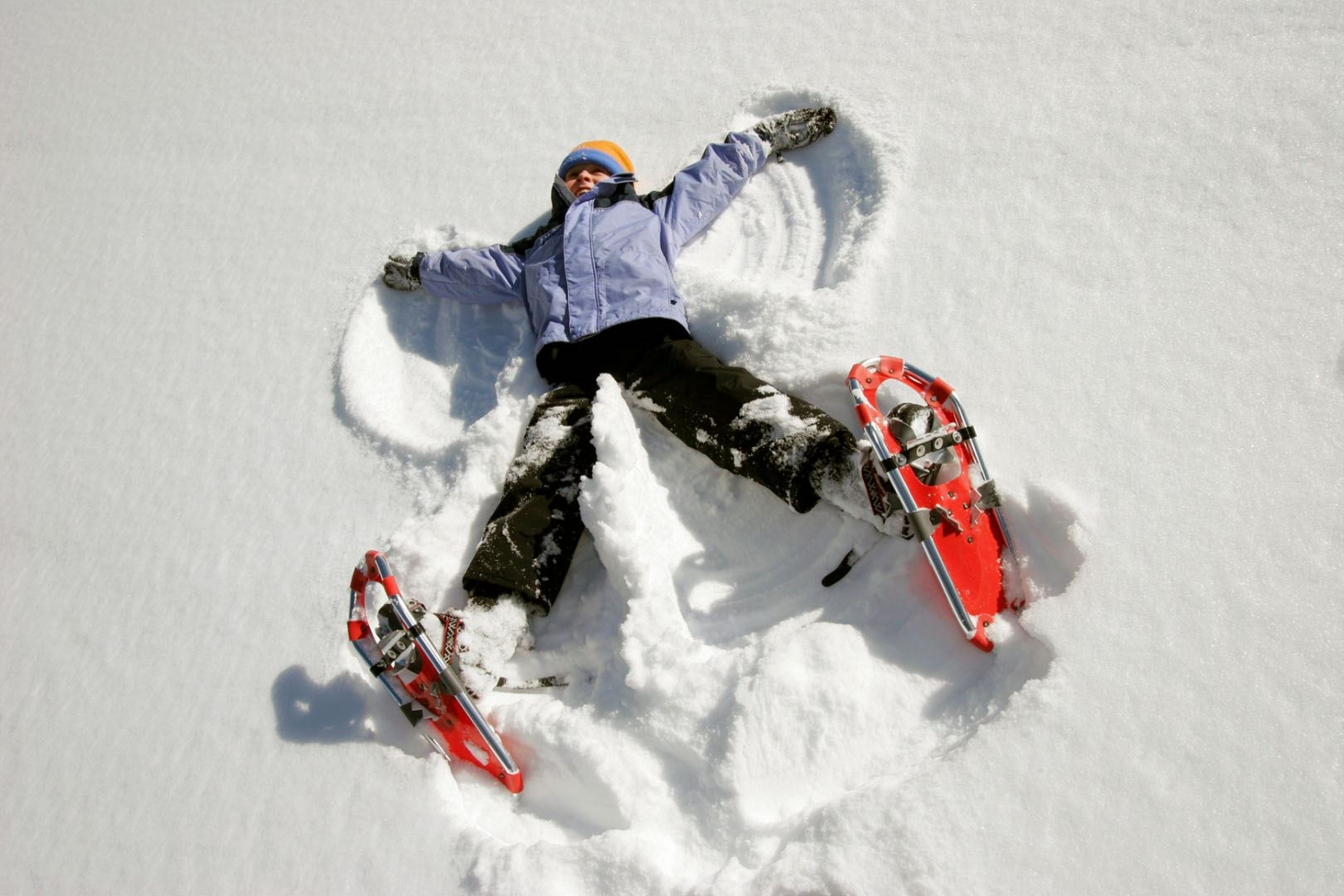 lady making snow angel in the snow