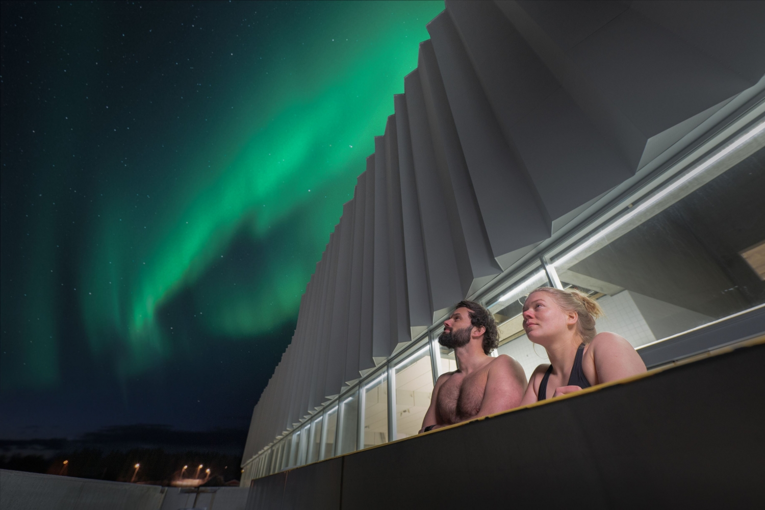 Man and woman in a pool under the Northern Light sky