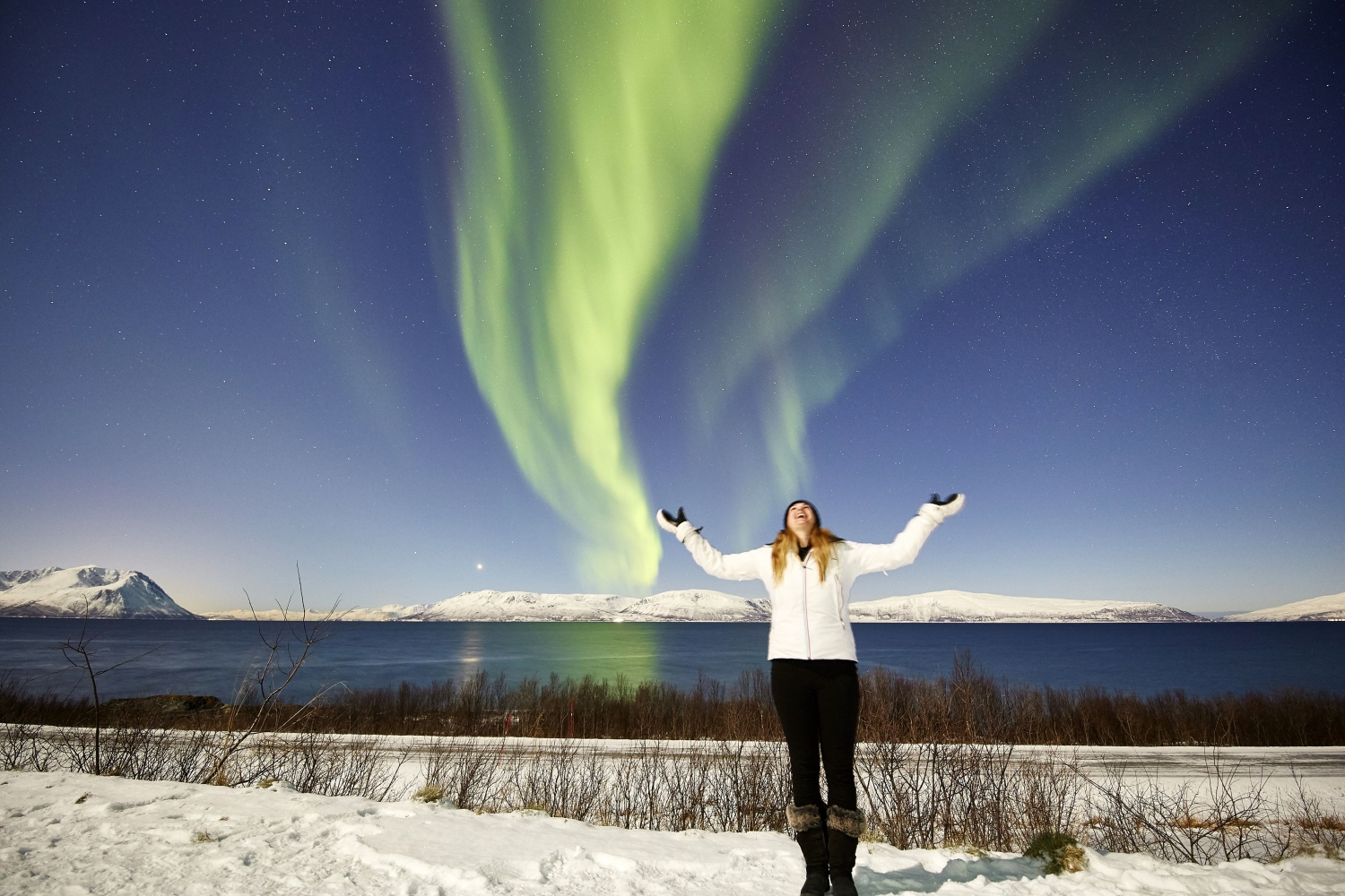 a woman standing with her arms up and looking at the sky where the northern lights are