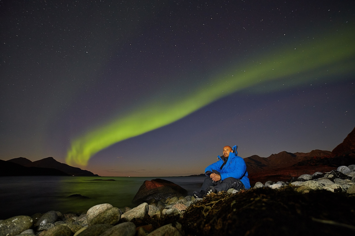 francisco is sitting by the sea with the aurora in the background