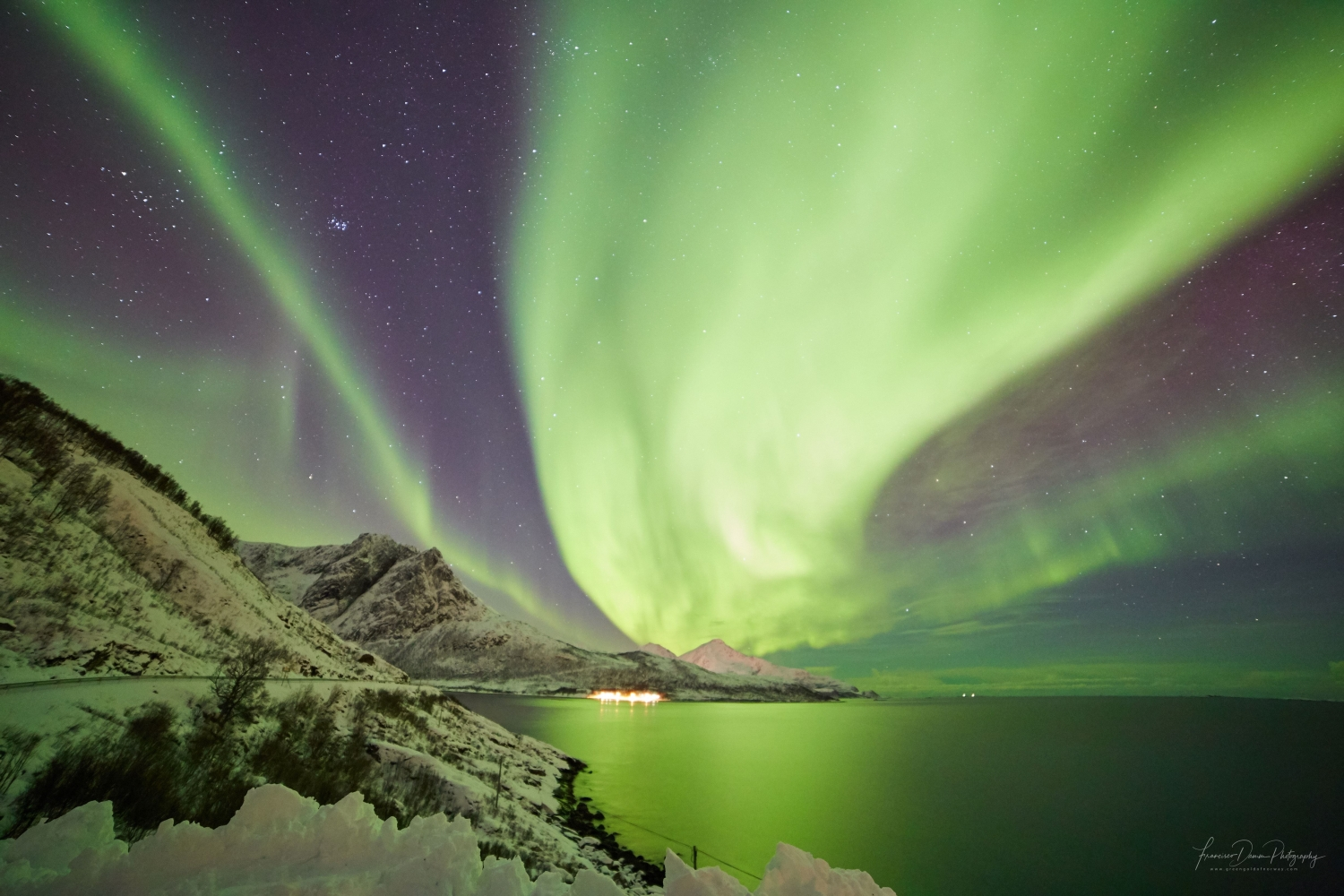 strong northern lights covering the whole sky over mountains and sea