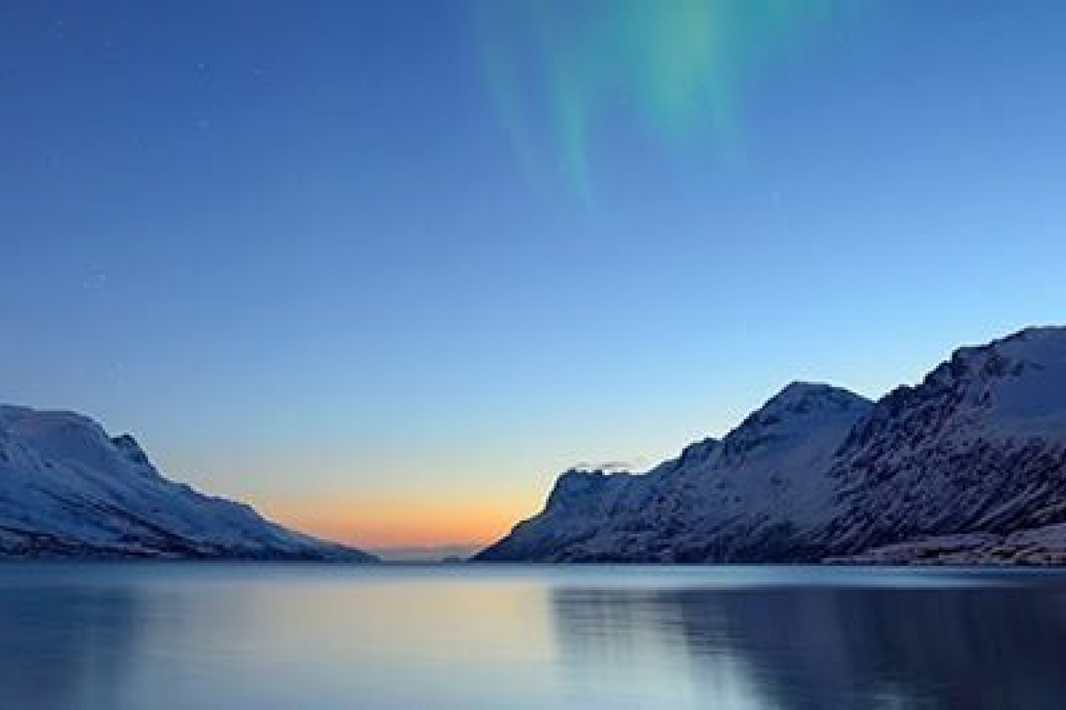 Fjord with silent ocean, snowy mountains and light from the sun below the horizon