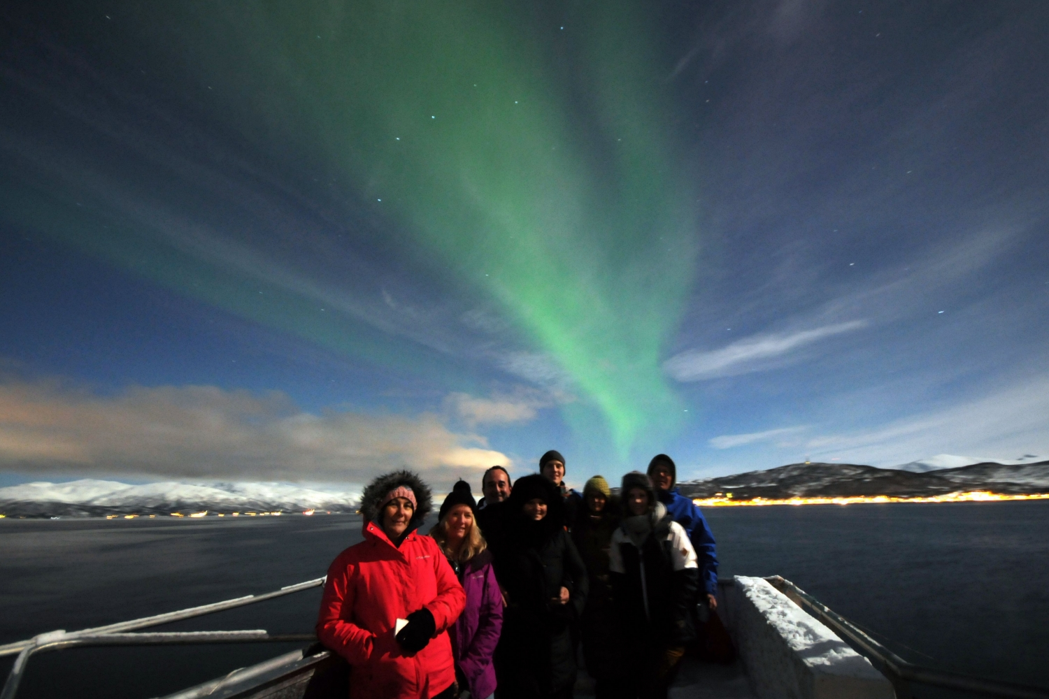 Guests on deck with Northern Lights in the background