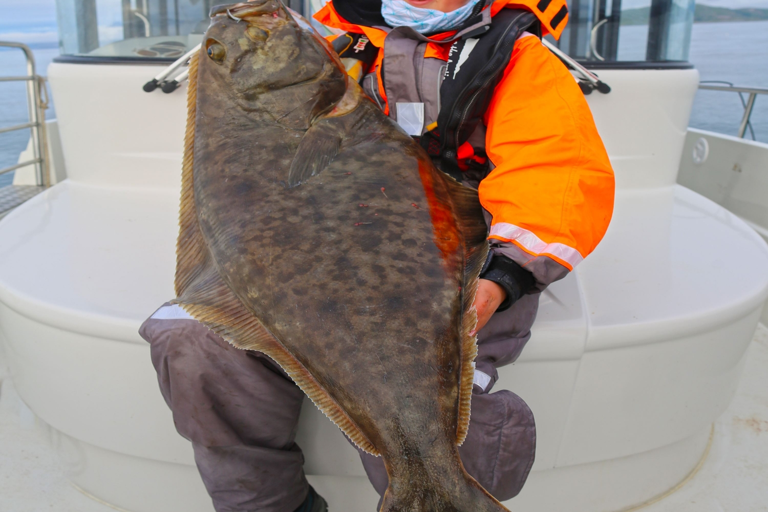 Person holding a halibut