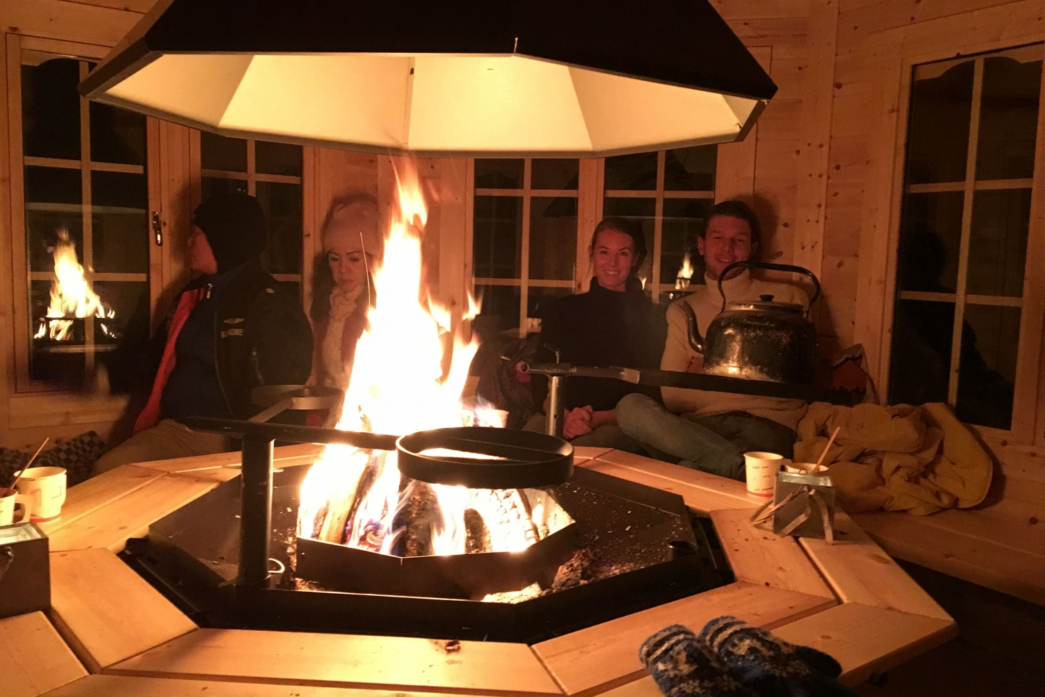 Persons sitting inside a hut with a bonfire in the middle