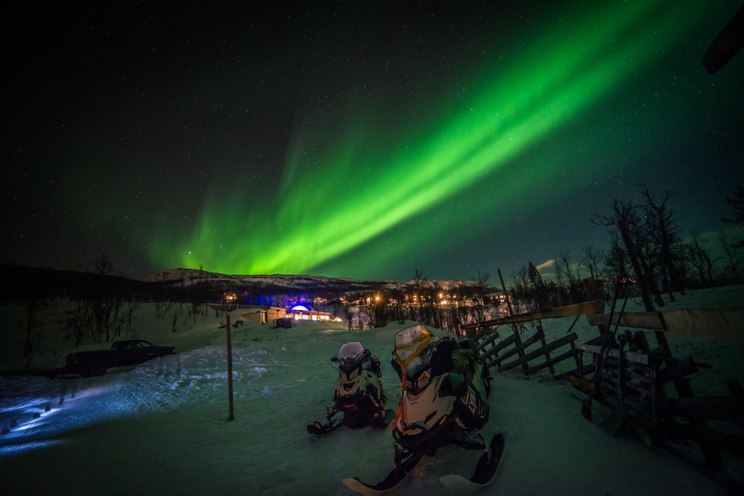 Northern lights above Arctic winter landscape, and snowmobiles