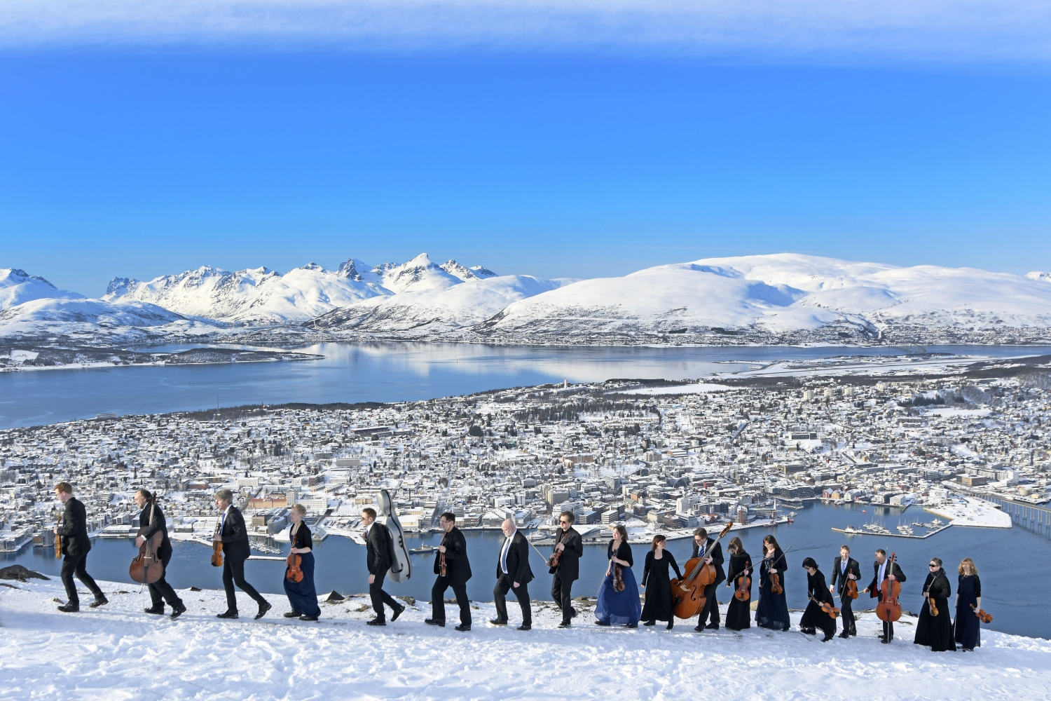 A parade of musicians carrying their instruments on top of the mountain Fløya, view over Tromsø island