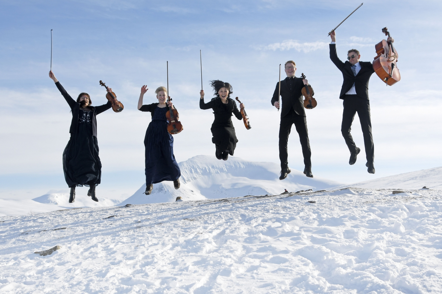 Five happy musicians with imusical nstruments jumping in the snow