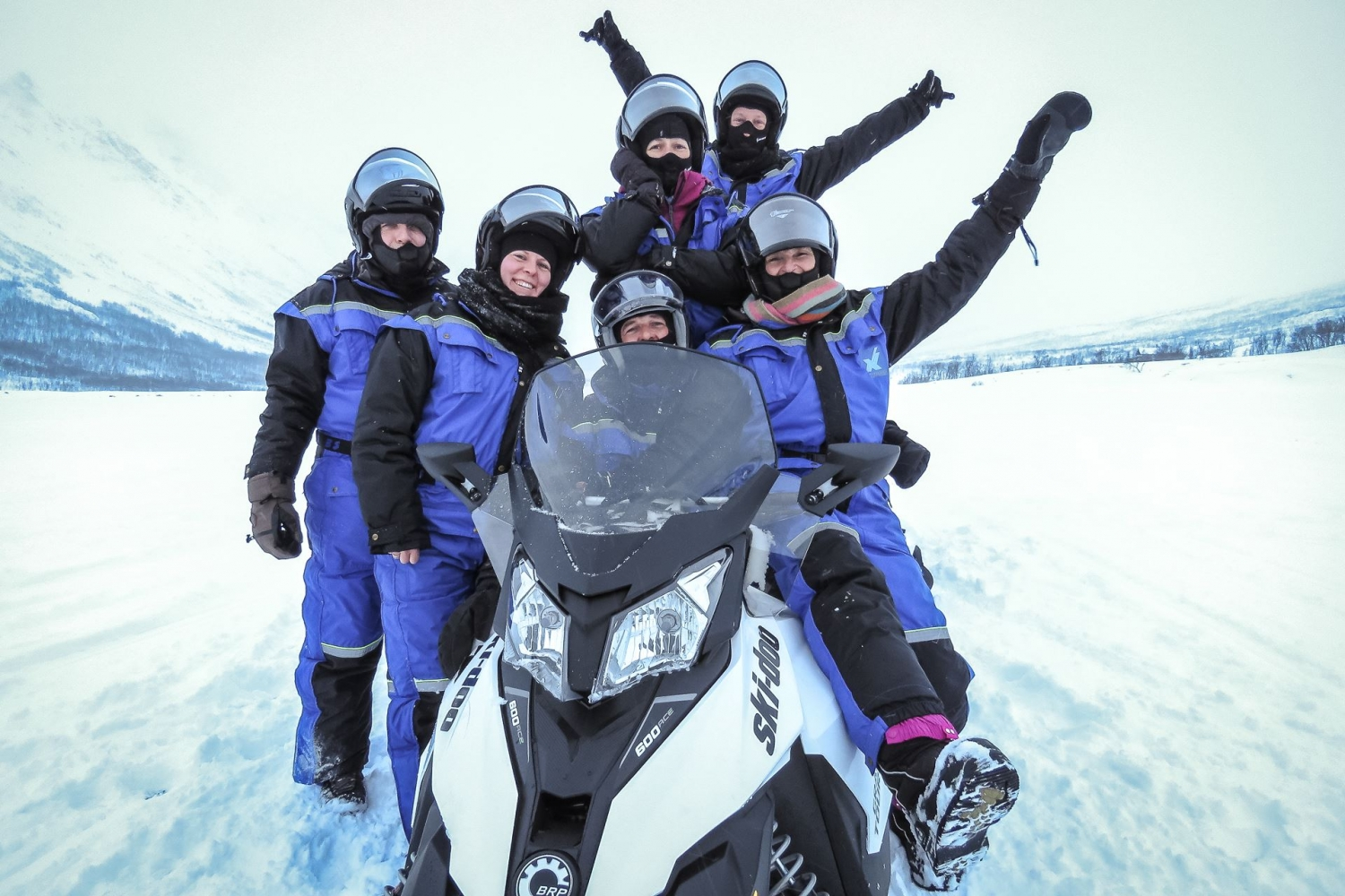 people posing around a snowmobile