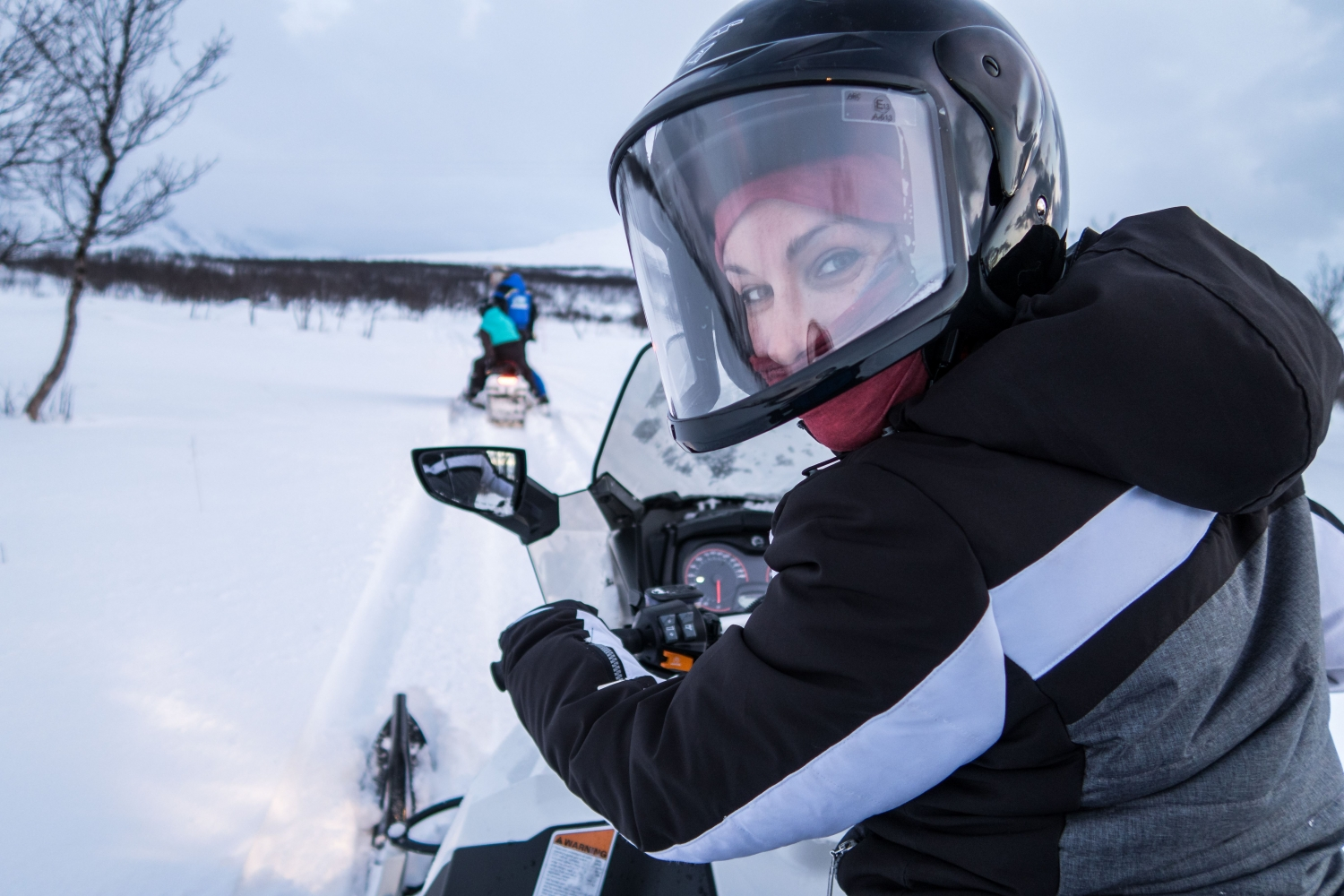 a woman driving a snowmobile