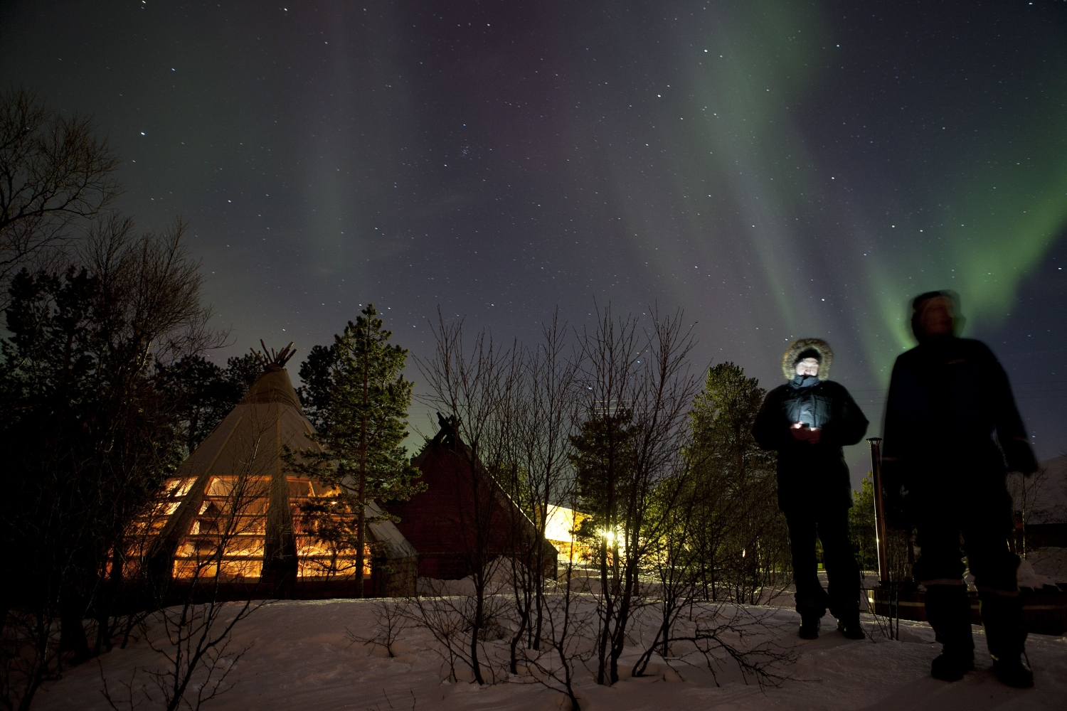 People standing outside of the gamme hut watching the Northern Lights