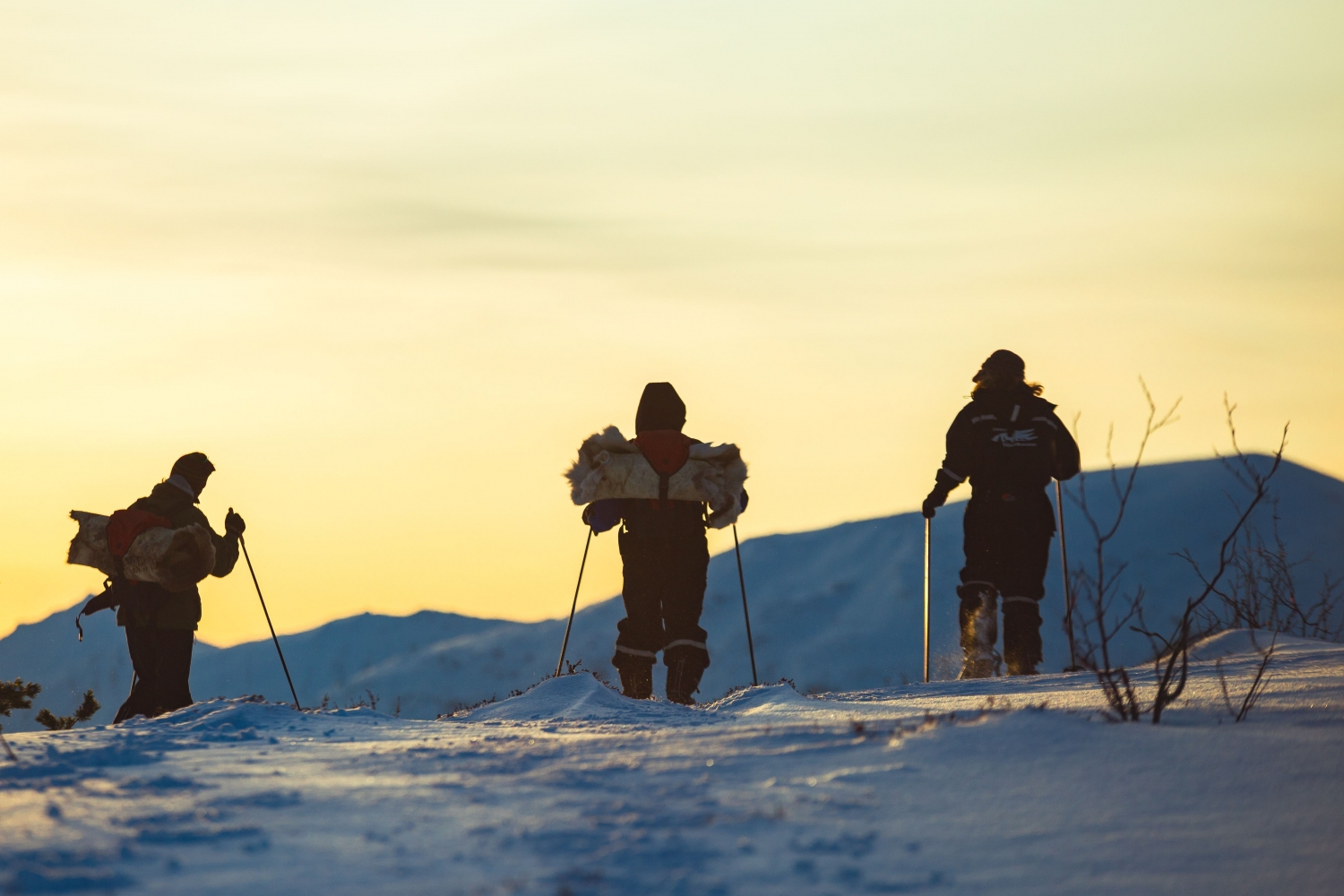 Three persons on snowshoes admiring the yellow coloured sky