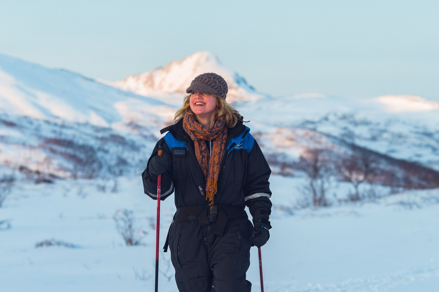 A woman snowshowing in a snowy Arctic landscape