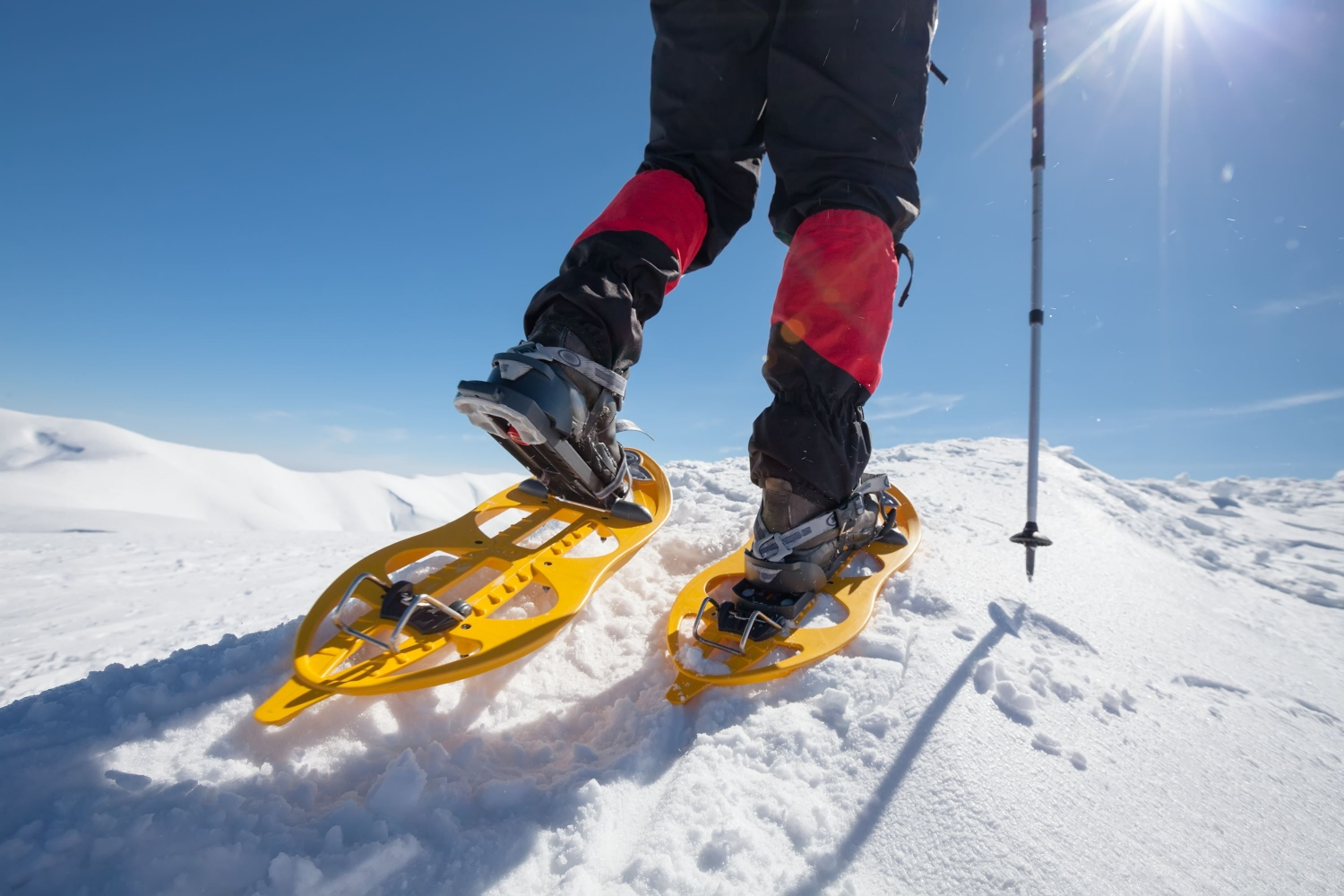 A persons feet with snowshoes on, sun in the background