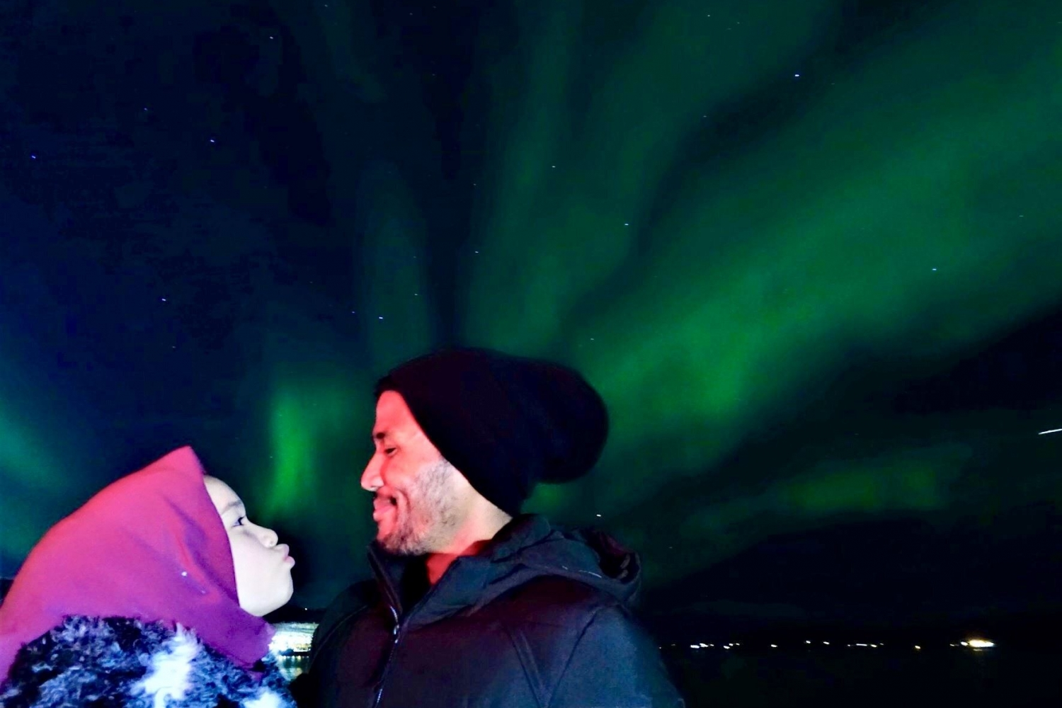 Two persons smiling at eachother with the Northern Lights in the background