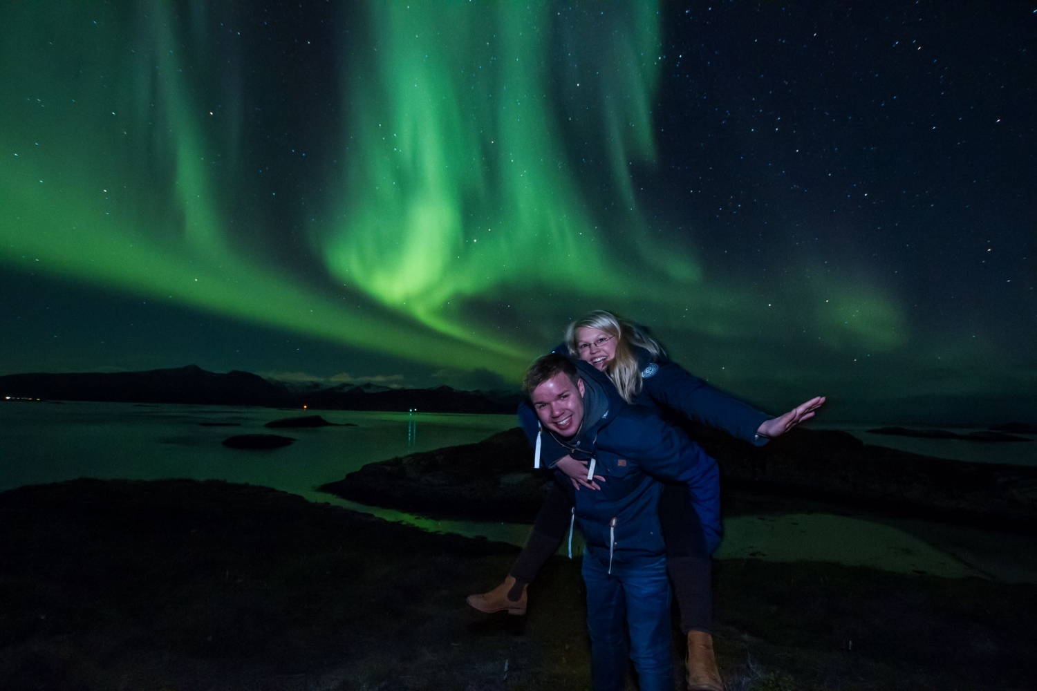 two people posing infront of the northern lights