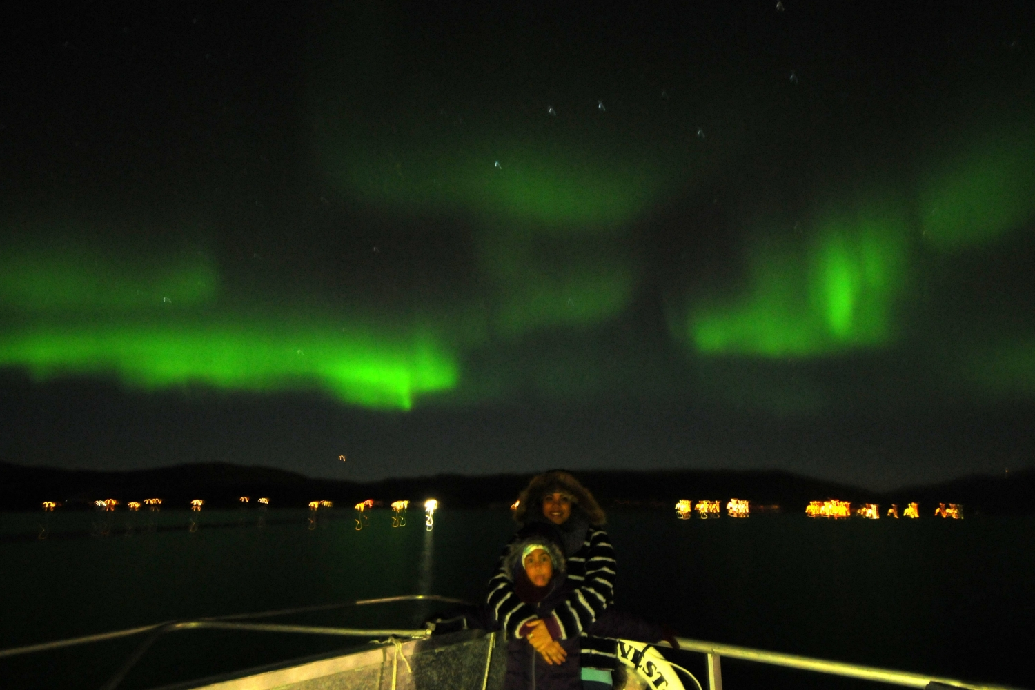 Couple out on deck with the Northern Lights in the background