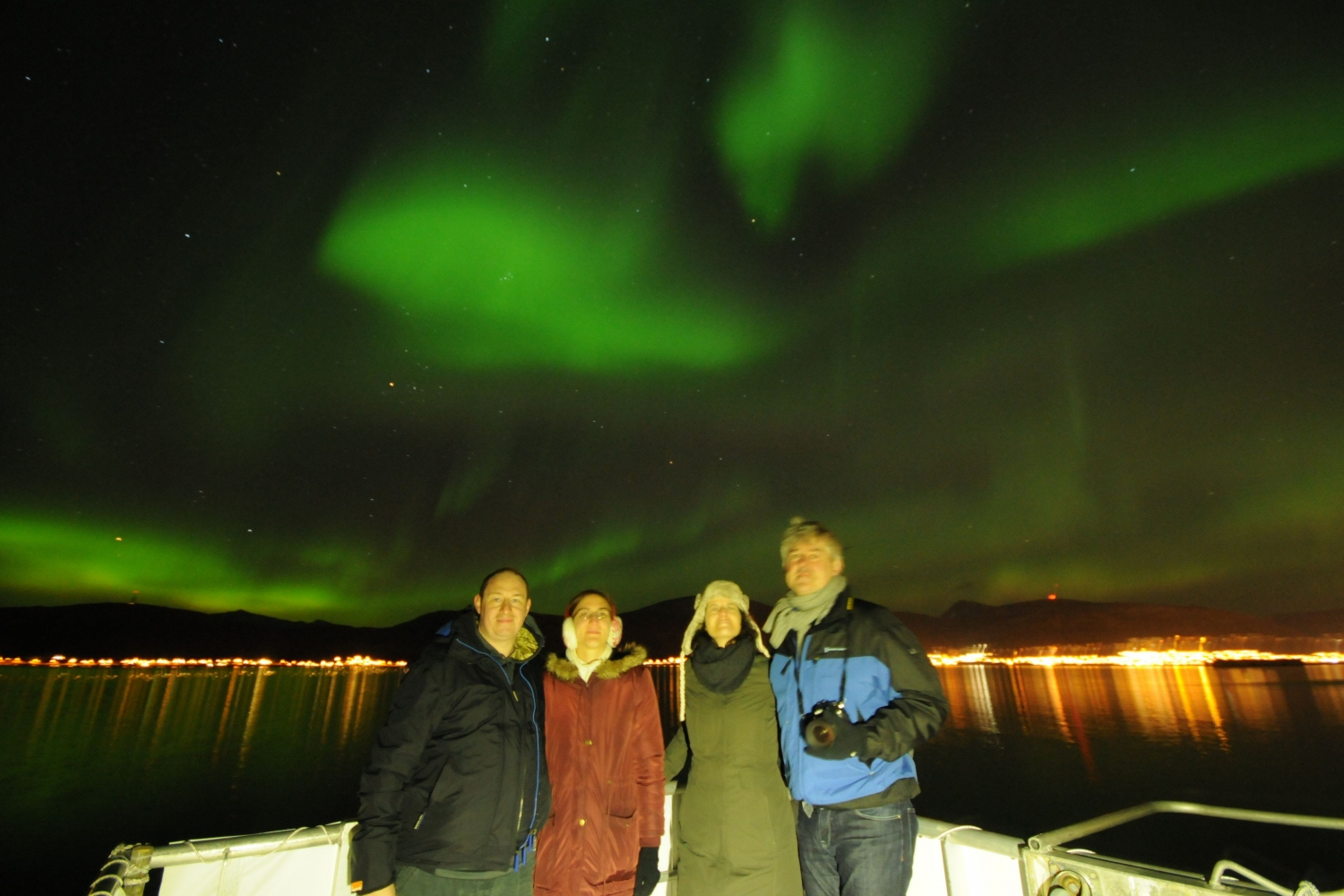 Four guests on deck with the Northern Lights in the background